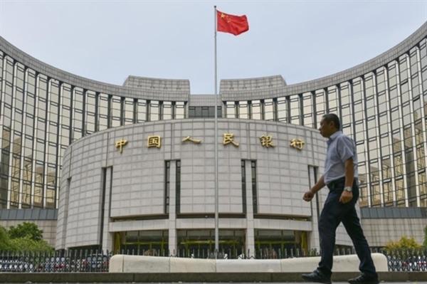 Người dân đi ngang qua trụ sở Ngân hàng Nhân dân Trung Quốc ở Bắc Kinh. Ảnh: China Daily.