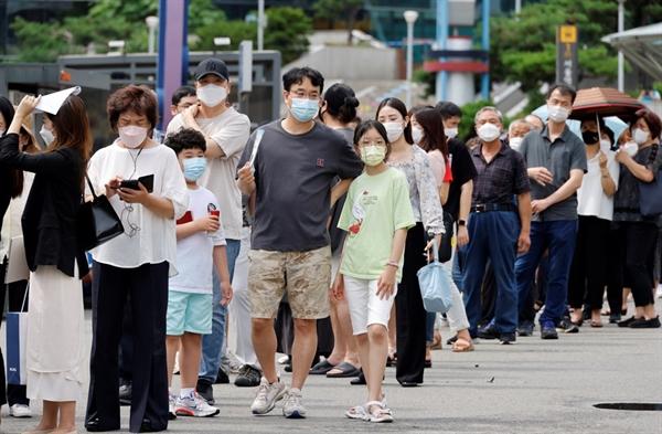 A1: Người dân xếp hàng chờ tiêm chủng tại một nhà ga xe lửa ở Seoul, Hàn Quốc. Ảnh: Reuters.