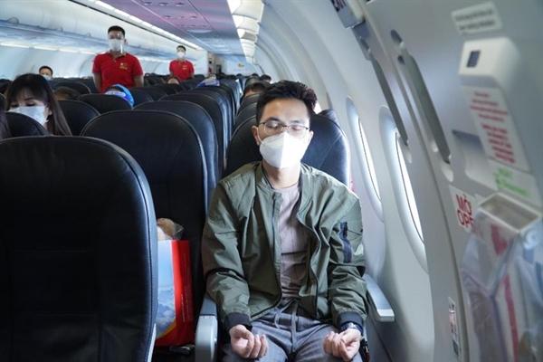 Hành khách trải nghiệm các bài tập yoga ngay trên tàu bay cùng với những động tác thở chậm, thư giãn, chuyển động nhẹ nhàng và thiền cho khách hàng một khoảng nghỉ ngơi. (Ảnh: Nguyễn Quang)