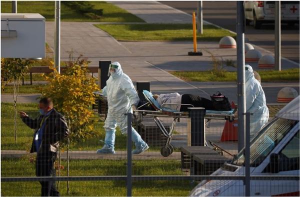 Các chuyên gia y tế vận chuyển một bệnh nhân bên ngoài bệnh viện cho những người bị nhiễm COVID-19 ở Moscow, Nga ngày 6/10/2021. Ảnh: Reuters.