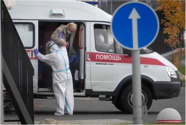 Một nhân viên y tế giúp đỡ một bệnh nhân bị nghi nhiễm COVID-19 tại một bệnh viện ở Kommunarka, ngoại ô Moscow. Ảnh: AP.
